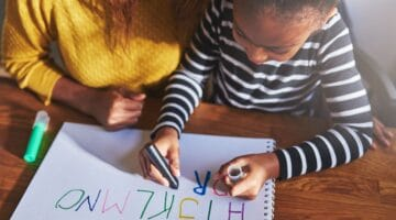 The Alphabetic Principle-a girl writing alphabet letters with her mother