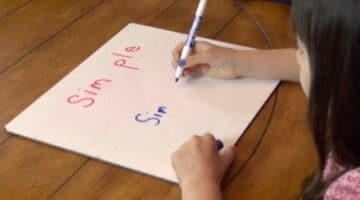 Multisyllable word reading practice on dry erase board